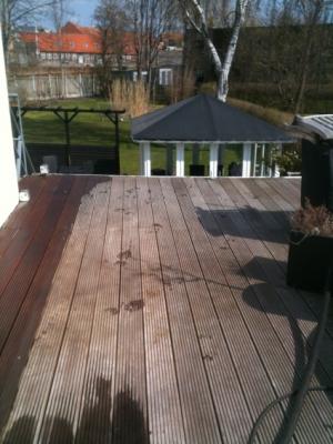 Her ses en en veranda i teak træ der trænger til behandling